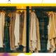 Schaufenster eines Geschäftes, in dem Kleidung in den Farben weiß, beige und dunkelgrün auf Kleiderständern aufgereiht sind