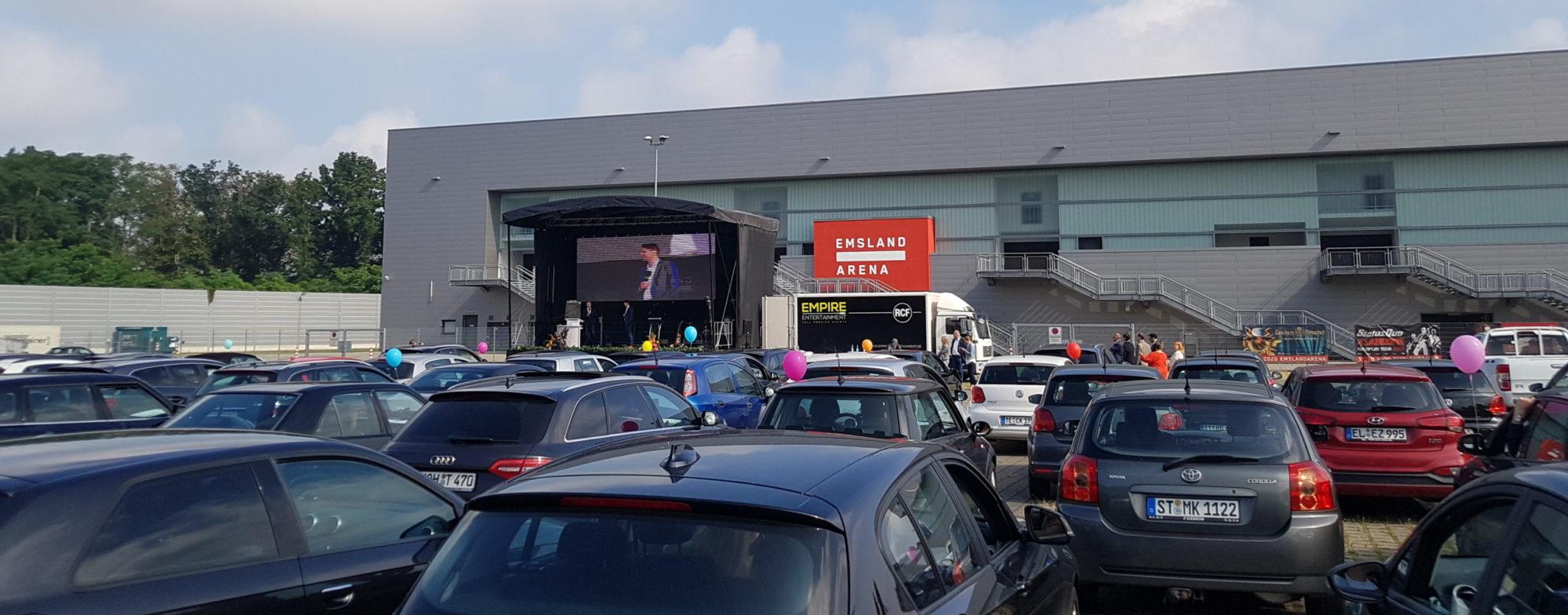 Autos stehen auf dem Parkplatz der EmslandArena vor einer Bühne. Abschluss