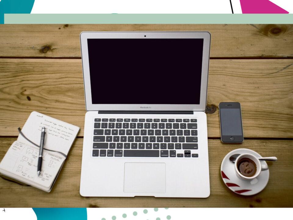 Laptop, Handy, Notizblock und eine Kaffeetasse