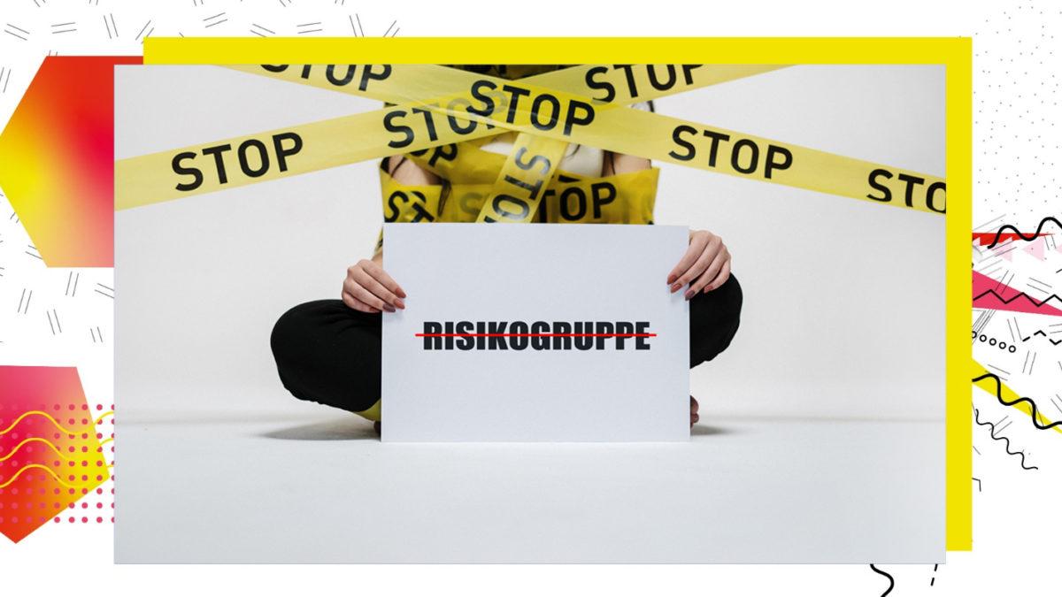 """Schild mit dem Wort """"Risikogruppe"""" wird von einer Frau gehalten"""