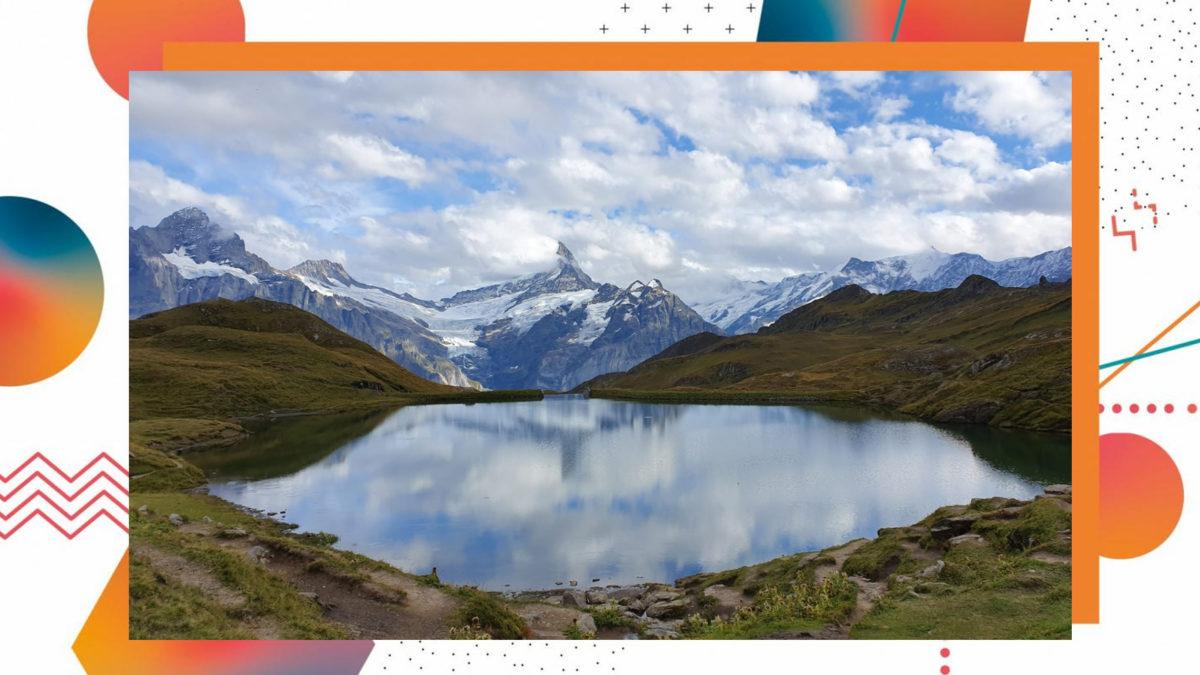 Ausblick auf einen See, im Hintergrund die schneebedeckten Alpen