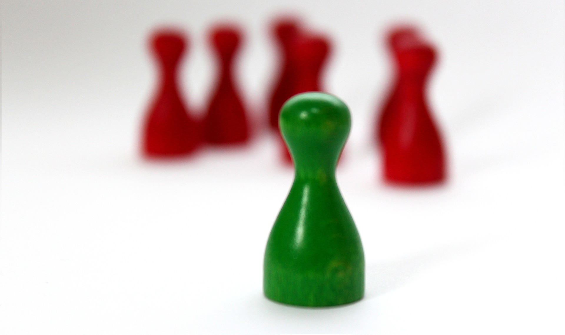 Im Hintergrund sechs rote Spielfiguren und davon isoliert im Vordergrund eine grüne Spielfigur.