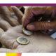 Zwei Hände von älteren Personen. Zwei 1 Euro-Stücke liegen in den offenen Hand.